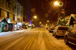 Snow falling in the glow of the street lights